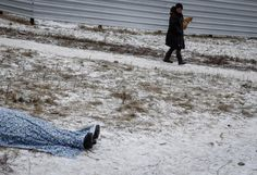 The body of a woman killed by recent shelling lies on a street in the residential sector in the town of Kramatorsk, eastern Ukraine, February 10, 2015. REUTERS/Gleb Garanich