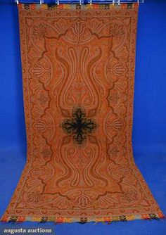 """WOOL PAISLEY SHAWL, 19th C   Long rectangle w/ black center, colorful tabbed end borders, 132"""" X 64"""", (small stain, minor moth damage) goog; t/w a red open field square w/ paisley border, field (moth damaged)poor, border good."""