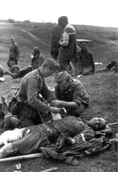 German medics of the 260th Infantry Division, Army Group Center(Heeresgruppe Mitte), assist wounded Soviet POWs during Operation Barbarossa; the Axis invasion of the Soviet Union. Romanischi, Gomel Region, Belarus, Soviet Union. July 1941.