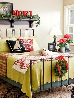 Red and green bedding paired with fresh greens create festive Christmas decor. Click to see more images of this house.