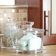 Here, a pair of glass jars provides pretty storage space for soaps and bath salts. For less attractive items, such as hair accessories and cotton swabs, search for stainless-steel or chrome containers. Their reflective surfaces will blend well with glass containers but will disguise the contents within.