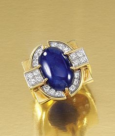 SAPPHIRE AND DIAMOND DRESS RING, PAUL FLATO, 1960S.  The bezel and shank of geometric design centring on an oval cabochon sapphire, embellished with lines of brilliant-cut diamonds, size N, signed Flato.