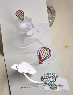 "By Maile Belles. Die cut a spiral from white cardstock. Attach ends to card. Randomly attach clouds and hot air balloons (from ""Up, Up, and Away"" by Papertrey Ink)."