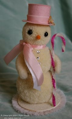 How cute for the holidays?! This little snowgirl is so pretty in pink. She wears a pink tophat and pink and white seam binding ribbons around