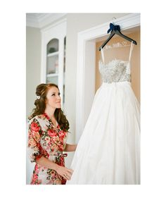 Bride's Gown Hanging: Before she slips into her dress, capture the bride taking it all in and admiring her special attire.  - 27 Must-Take Wedding Photo Ideas