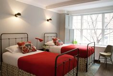 Red bed sheets, gray walls, black iron beds, wrought iron beds and mounted lights!