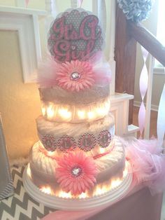 Pink, gray, & white diaper cake with white lights that I made for a baby shower. Some pieces were made using  Cricut Explore. Base of cake is a ceiling medallion used under ceiling fans. Got it at Home Depot. It's perfect because it's so sturdy making the cake so easy to carry & transport. Get it here: http://www.homedepot.com/p/Westinghouse-16-in-Beaded-White-Finish-Ceiling-Medallion-7773300/203077499