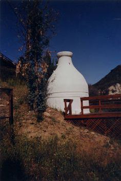 This water tank built by T. W. (Bill) Kneen in the shape of a milk bottle was built in the 1930's out of masonry. Located at Red Rock Road, Old Topanga Canyon. Photographer: A. Les Haines. Topanga Historical Society. San Fernando Valley History Digital Library.