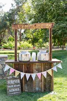 Temecula wedding at the lake oak meadows winery ceremony set up with brown wood lemonade stand with colored flag hanging decor and sign