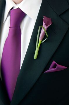 A purple calla lily becomes modern when accented with a thin architectural leaf in this groom's boutonniere.