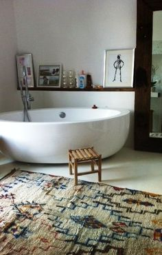 Beautiful oval vessel bath tub, very clean and contemporary look toned down with Navajo style rug; nice natural wood ledge for art, candles and a drink!