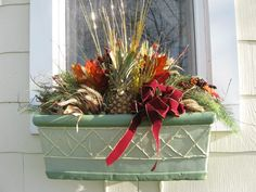 The pineapple is a symbol of hospitality. I decorated my window boxes with bittersweet fresh greens and corn husks for a fall into winter welcome.