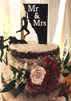 Rock climbing cake topper on a semi-naked wedding cake with flowers. It actually looks pretty cute