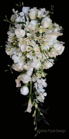 This all white teardrop cascade style bouquet features white dendrobium orchids, white roses and white freesia.