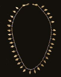 A ROMAN GOLD AND GLASS NECKLACE Circa 2nd-3rd Century A.D. Composed of lengths of figure-8 loop-in-loop chain, interspersed with forty-nine blue glass beads and thirty-four leaf-shaped sheet pendants, with a hook-and-loop closure, each with a leaf-shaped sheet attached 17¾ in. (45.1 cm.) long