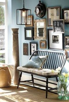 A fun, eclectic family frame gallery and comfortable bench make for a cozy and warm hallway. | Pottery Barn