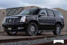 This black #Cadillac Escalade is all about showing off its chrome style. Inside sits a sea of comfortable leather and high tech luxury features to make driving a breeze. Under the hood sits a big 6.2-liter Vortec 6200 V-8 engine sending a total of 403 horsepower to the new #DUB wheels for the monster SUV. http://www.wheelhero.com/rims-and-tires