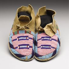 Crow Moccasins, 1890. of one-piece side seam construction, sinew sewn, each decorated on the vamp with a pair of horizontal bands, and with typical bands partially encircling the foot, soft soles. The side seam tailoring is atypical of Crow moccasins from this time period and might suggest a Plateau attribution. However, the distinctive Crow design scheme and color choices argue for the latter. Collected by A.C. Flegal, Old Miles Town, MT. Heritage Auctions. 2007 Dallas, TX