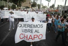 """Image: A protester holds a sign reading, """"We want Chapo free"""" during a march in Culiacan"""