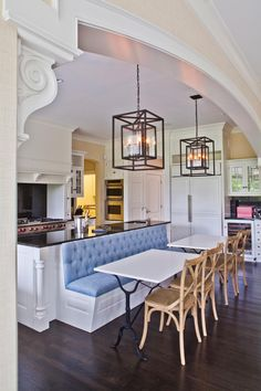 Cutting the breakfast island in this kitchen down to half its original size opened up more space and allowed room for two breakfast tables. The vintage-style tables are complemented by chic light fixtures and a custom banquette.