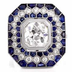 This elaborately designed Art Deco design engagement ring of captivating beauty is crafted in solid platinum. Designed as a geometrically inspired octagonal plaque of contrasting colors, it is centered with a prominent 2.15ct antique cushion-cut diamond, graded H color and VS2 clarity, surrounded by a gorgeous mosaic design of 44 trapezoid-cut sapphires of approx. 2.65ct and 32 round-faceted diamonds weighing 0.65cts, graded H-I color and VS1 clarity. With a sleek, sizable shank and an…