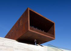 Granite bleachers climb the exterior of this sports centre in Portugal, while a cantilevered, rusted-steel cafe looms over its entrance.