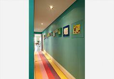Outro ambiente que costuma ser esquecido por ser muito estreito é o corredor. Também no projeto de Bruna Riscali, o espaço foi valorizado com cores nas paredes e na passadeira. Na parede, obras de arte