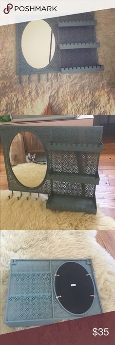 "Urban Outfitters Hanging Storage Hanging storage with mirror. Has three shelves and 5 hooks for purses/jackets/etc. Color is listed as teal but definitely has some grey tones. Great condition, just has one nick at the top (see image). 17"" in length and approx 13"" in height. Not interested in trading. Thanks for looking! Urban Outfitters Other"