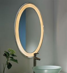 Tech Lighting Tigris 700BCTIGO Oval Lighted Mirror    Oval mirror surrounded by a cove of diffused white light. Available in recessed or surface mounted. Plated pressure formed frame. Provides shadow-free task and ambient light. Halogen includes transformer and 12 volt, 20 watt Halogen bi-pin lamps; compact Fluorescent includes 9 watt 2G7 base twin tube lamps and electronic ballast. Halogen version dimmable with a standard Incandescent dimmer.