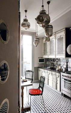 Parisian kitchen with Fornasetti pilasters printed on cabinet doors, door with round windows in spirit of Jean Prouvé, mercurial glass pendant lights & Fornasetti wallpaper from Cole & Son protected by Plexiglas in credenza.