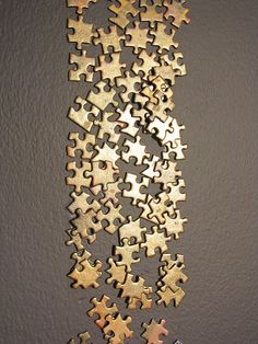 Gold painted jigsaw pieces on a wall