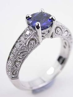 Filigree Engagement Ring with Blue Sapphire, RG-1747y, A natural blue sapphire is prong set above two hearts on the under bezel. The band has a lovely paisley filigree design with diamonds. Matching wedding bands are available for separate purchase.   <p>Details: 18k white gold. Round full cut diamonds; 0.30 carats. Round blue sapphire; 0.84 carats. Antique style (New).</p> Ring Size 6.0