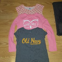 "Girls Old Navy tops Bundle of three size large tops.  One is sleeveless patterned in corals and white with a cute tie on the bottom middle and buttons up the front.  One is a graphic long sleeve tee in pink with a white glitter owl that says ""who me?""  One is a short sleeve grey high low tee with Old Navy in yellow Old Navy Shirts & Tops Tees - Short Sleeve"