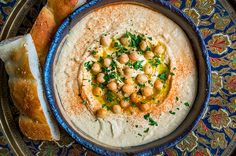 THE BEST BASIC HUMMUS RECIPE In Dairy free, Gluten free, Vegan, Vegetarian  Serves 6-8 as a starter  2 x 400g cans of chickpeas (reserve the liquid and a few chickpeas for decoration) 4 tsp tahini 2 garlic cloves, crushed 1 tsp crushed sea salt 6 tbsp quality extra virgin olive oil (plus extra for drizzling) 3½ tbsp freshly squeezed lemon juice Paprika (optional) Coriander or parsley leaves (optional)
