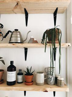 DIY shelves: I Silvan købte vi 2 Kalmar brædder og 12 sorte hyldeknægte (15 x 12,5 cm.), skruer, rawplugs og en semi blank træ-lak havde vi i forvejen og da vi godt vidste at hylderne max skulle måle 90 cm., lånte vi en sav i Silvan og savede dem over,