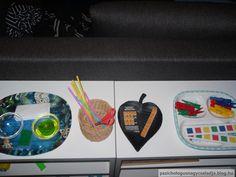 Montessori polc tálácákkal 2-3 éveseknek. Balról jobbra: folyadék átvitel szivaccsal, szívószál vagdosás ollóval, matrica ragasztás, csipeszek elhelyezése színes csíkon. Finommotorika, színfelismerés, sorozat. Montessori shelf for 2-3 year olds. Fine motor skills, sponging, cutting, color recognition, sequencing skills.
