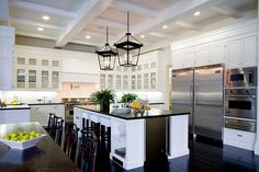 Eat in kitchen in a Spanish revival home with two lantern lights, white cabinets with glass fronts, coffered ceiling, stainless appliances and a white island with black countertops