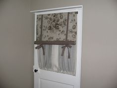 rolled swedish blind with voile panel behind to offer privacy for this bathroom door