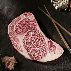 An example of both the marbling on wagyu beef, and how this looks contrasted on a dark background, the red white and grey work together well.
