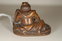 WOOD NETSUKE By Shoju. Depicting a nio tying a sandal. Lengt