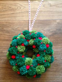 Pom pom wreath with different shades of green pom poms, and small red pom poms to look like berries.