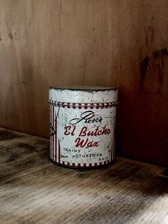 Need a retro tin container that once held pomade for creating a butch hair cut? I have this distressed metal container for your home or barbershop decor. Roses El Butcho Wax  Trains Stubborn Hair big 3 ounce can size. Roses Cosmetic Products Waterloo, Iowa Fun advertisement tin from the 1950s when this hair style was most popular. This is an empty tin, all surfaces are aged and distressed. 2 1/8 tall 2 diameter can.