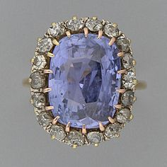 A sapphire and diamond cluster ring The oval mixed-cut sapphire bordered by eighteen old brilliant-cut diamonds