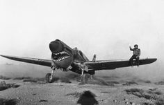 fcba:  A mechanic sits on the wing of a British P-40 Kittyhawk to help it taxi in a Libyan sandstorm on April 2, 1942. (AP)