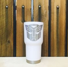 White Laser etched Transformers RTIC Tumbler  We promise all your friends will be asking you where got that awesome tumbler.  Why get a laser etch tumbler over a screen printed one? We custom laser etch each tumbler with a special chemical that burns the design permanently in black. This means you can wash it over and over and the logo will NEVER rub off. Screen printing can fade and chip off over time. Laser etching will be there for life!  About RTIC Tumblers: RTIC Tumblers are stainless…
