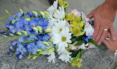 hand tied wedding bouquet of white daisies, pink dendrobium or orchid, green astromeria, and blue delphinium by reynoldstreasures.com