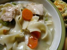 SLOW COOKER CREAMY CHICKEN NOODLE SOUP (serves 8): 4 C cooked chicken,   1 C onion,   1 C celery,   1 C carrot,   1/2 C frozen peas,   4 (14 ounce) cans low sodium chicken broth,   2 (10 3/4 ounce) cans condensed cream of mushroom soup w/roasted garlic,   2 tsp fines herbes (chives, parsley, and tarragon) salt,   pepper,   2 cups egg noodles, cooked