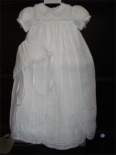 This is an elegantly, simple long Christening gown by Feltman Brothers for Baby girls. It is made with white cotton fabric and trimmed around the neck, sleeves, and bottom of the skirt with delicate lace.