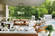A poolside lounge features a pendant lantern by Ames Ingham and a barrelback chair from Dennis Miller Assoc.; the Robert Bristow dining table and benches are from Ralph Pucci International, and the cushions on the sofa, lounge chairs, and dining chairs are covered in a Perennials fabric.