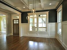 dark walls are softened with white wainscoting and coffered ceiling also painted in white.